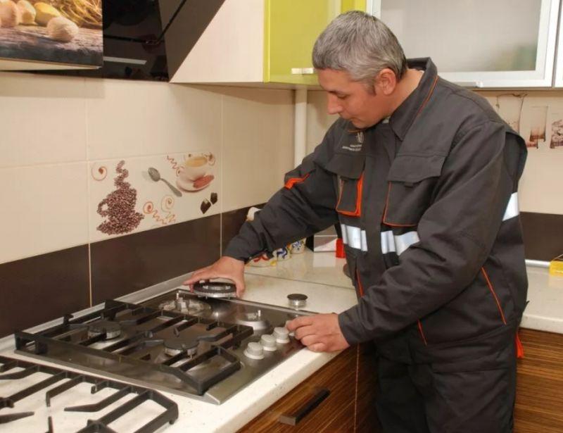 Газовщик ремонтирует плиту